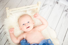 2 month baby smiling covered with blue textile Stock Images