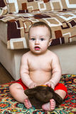 10 month child sitting with toy and looking ahead Stock Photos