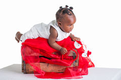 Toddler playing on a red crate. A 8 month old baby dressed to explore Christmas Stock Photo