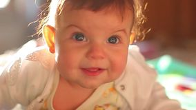 6 month old baby lies on the bed and smiles charmingly. Little blue-eyed kid at home stock video