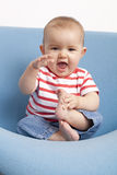 8-month old baby playing with feet. Playful baby boy smiling on blue seat Stock Photos