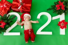 A 6 month old baby in a Santa costume lies on a green  background with the inscription 2021 and gifts