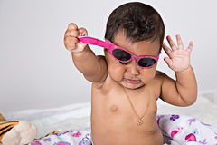 7 month old baby trying to take off sunglasses Stock Photography