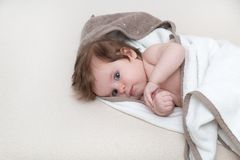 3 month old baby wrapped in towel on white background looking at you. Happy childhood concept Royalty Free Stock Images