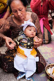 A 3-month-old Balinese-Hindu baby boy is dressed by his family in Hindu religious clothing during his baby-naming ceremony in Bali Stock Image