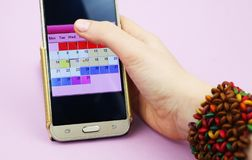 A woman holds a mobile phone with a menstruation calendar royalty free stock photography