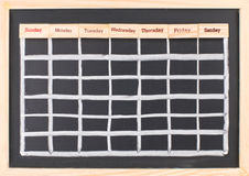 Monthly calendar with week words print. On wood on blackboard Royalty Free Stock Photos