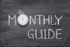 Monthly guide watch. Monthly guide handwritten on chalkboard with vintage precise stopwatch used instead of O Royalty Free Stock Images