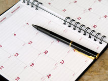 Monthly planner. With pen on the table Stock Image