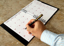 Monthly planner. Man filling out  monthly planner on the table Stock Photo