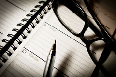 Monthly planner. With pen and black glasses royalty free stock images