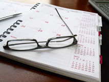 Monthly planner with glasses. Monthly planner with reading glasses and pen on the table Stock Photography