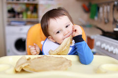 18 months baby eats pancakes stock photo