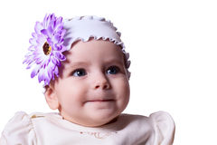 6 months baby girl with a flower on her head smiling on a white. 6 months baby girl with a flower on her head in white dress smiling on white background Stock Photos