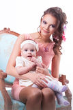 6 months baby girl sitting on the lap of a joyful mother and kee. 6 months baby girl sitting on the lap of a joyful mother in a pink dress and holding a finger royalty free stock image