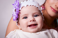 6 months baby girl smiling with a flower on her head. Wearing a white blouse and a white ribbon on his head, in mother's arms Stock Image