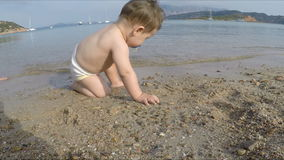 10 months baby playing with sand on the beach stock footage