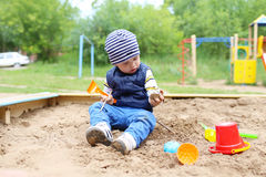 21 months baby playing with sand. Lovely 21 months baby playing with sand on playground in summer Royalty Free Stock Image