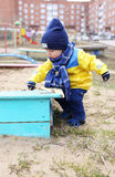 18 months baby playing with sand on playground. In spring Stock Image