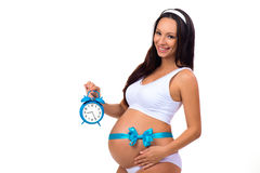 9 months. Happy pregnancy. Pregnant woman with alarm clock in his hands and blue bow on the tummy Royalty Free Stock Photo
