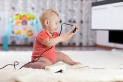 8 months old age baby pulling cables from electrical extension. 8 months old age baby boy pulling cables from electrical extension Royalty Free Stock Photo