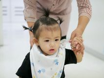 Asian baby girl learning to walk with help from her mother royalty free stock photo