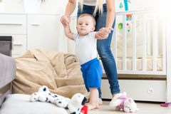 10 months old toddler boy learning making first steps with mother. 10 months old baby boy learning making first steps with mother royalty free stock images