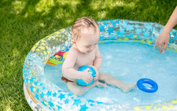 9 months old baby boy playing with ball in pool at garden. Cute 9 months old baby boy playing with ball in pool at garden stock image