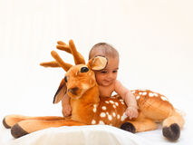 4 months old baby boy playing with soft toy dear and chick Stock Photography