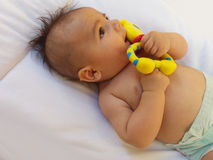 3 months old baby boy playing with teething toy. Giraffe, white background Royalty Free Stock Photos