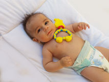 3 months old baby boy playing with teething toy. Giraffe, white background Royalty Free Stock Photo