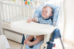 10 months old baby boy sitting in highchair and crying. 10 months old baby sitting in highchair and crying Stock Photo