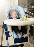 0 months old baby boy sitting in highchair. At kitchen Royalty Free Stock Image