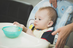 9 months old baby boy sitting in highchair and reaching for dish. Portrait of 9 months old baby boy sitting in highchair and reaching for dish Royalty Free Stock Photos