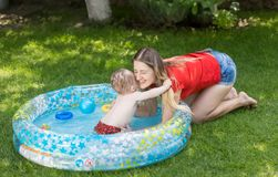 Adorable 10 months old baby boy swimming in in flatable pool hugging his mother. 10 months old baby boy swimming in in flatable pool hugging his mother stock photography