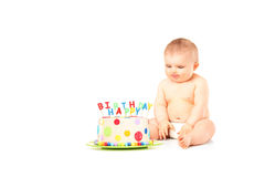 A 9 months old baby in diapers sitting next to a birthday cake Stock Image