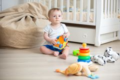 10 months old baby boy sitting on wooden floor at bedroom and playing with toys stock images