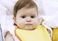 9 months old cute baby sitting in a highchair is upset and refuses to eat complementary foods. Closeup portrait royalty free stock images