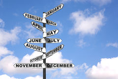 Months of the year signpost. A directional signpost showing the months of the year against a blue cloudy sky stock images