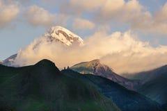 Monti la chiesa di trinità di Gergeti e di Kazbek nella luce dell'alba Fotografie Stock