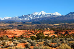 Monti-La Sal National Forest of Utah. Snowcapped Mount Tukuhnikivatz of the Monti-La Sal National Forest rises above the red rock landscape in Utah stock image