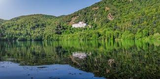 Monticchio sjö med den berömda abbotskloster och Monte Vulture, Basilicata, Italien royaltyfri bild