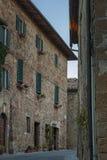 Montichiello -意大利, 2016年10月29日:静街在Montichiello,有典型的被关闭的窗口和被铺的街道的托斯卡纳 免版税库存图片