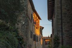 Montichiello -意大利, 2016年10月29日:静街在Montichiello,有典型的被关闭的窗口和被铺的街道的托斯卡纳 免版税图库摄影