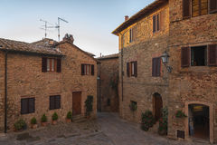 Montichiello - Italië, 29 Oktober, 2016: De stille straat in Montichiello, Toscanië met typisch shuttered vensters en bedekte str stock foto's