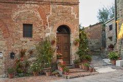Montichiello - Italien, Oktober 29, 2016: Tyst gata i Montichiello, Tuscany med typiska stängde med fönsterluckor fönster och ste royaltyfria bilder