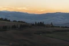 Montichiello - Toscanië/Italië: 29 oktober, 2017: Het winden van Cipres gevoerde weg in Monticchiello Royalty-vrije Stock Foto's