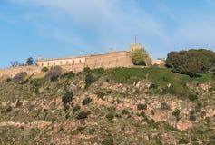 Montjuic fästning som förbiser den Barcelona hamnen från porten arkivfoton