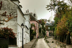 Montmartre district of Paris. House on narrow road in Montmartre district of Paris with Sacre Coeur Basilica in background, France Stock Photos
