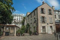 Montmartre's gränd med byggnadsfasaden och järnport i solig dag för sen eftermiddag på Paris arkivbilder